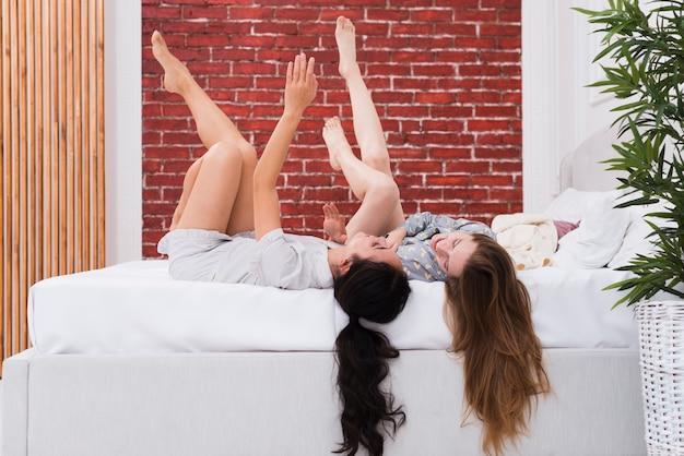 Juguetona mujer acostada en la cama con las piernas en alto
