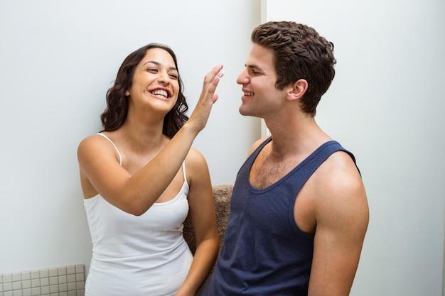 Juguetona mujer aplicando crema en la nariz del hombre
