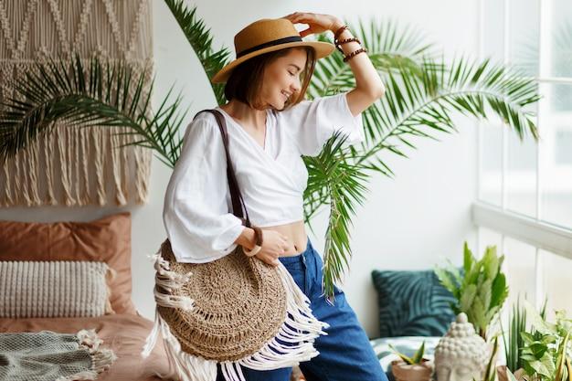 Juguetona mujer bohemia posando en un elegante dormitorio con interiores increíbles, palmeras y macramé