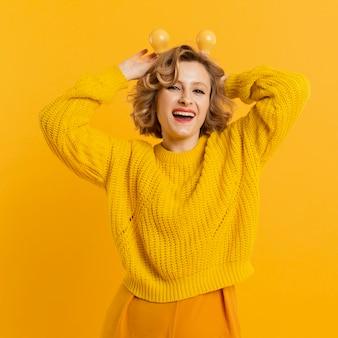 Juguetona mujer con bombillas amarillas