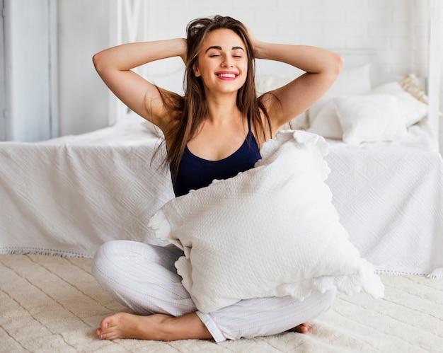 Juguetona mujer en la cama con los brazos alzados