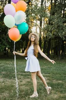 Juguetona mujer de cumpleaños con globos