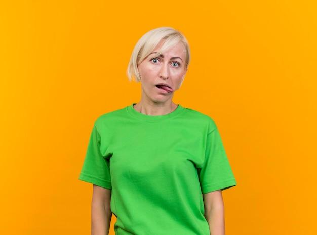 Juguetona mujer eslava rubia de mediana edad mirando al frente mostrando la lengua aislada en la pared amarilla con espacio de copia