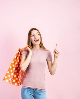 Juguetona mujer en jeans con fondo rosa