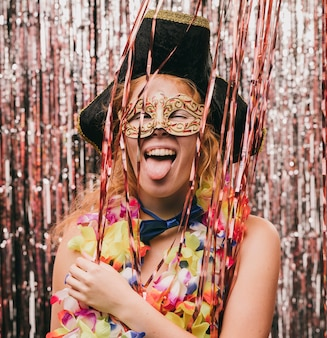 Juguetona mujer sonriente vestida en fiesta de carnaval