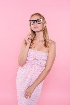 Juguetona mujer sosteniendo la máscara con gafas