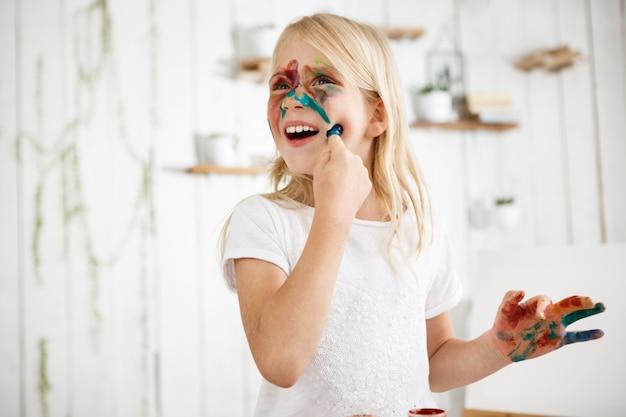 Juguetona niña rubia de siete años tocando su rostro con el dedo en la pintura. la niña se pintó la cara con diferentes colores. jugando niño