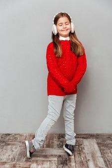 Juguetona niña sonriente en orejeras de pie y bailando