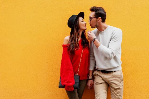 Juguetona pareja de enamorados posando sobre pared amarilla. gente viajera. chica morena con novio guapo viajando en europa.