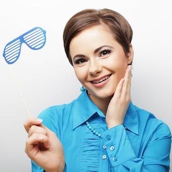 Juguetonas mujeres jóvenes sosteniendo una fiesta gafas.