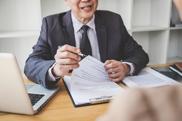 Junta leyendo un currículum durante una entrevista de trabajo, empleador entrevistando a una joven mujer que busca trabajo