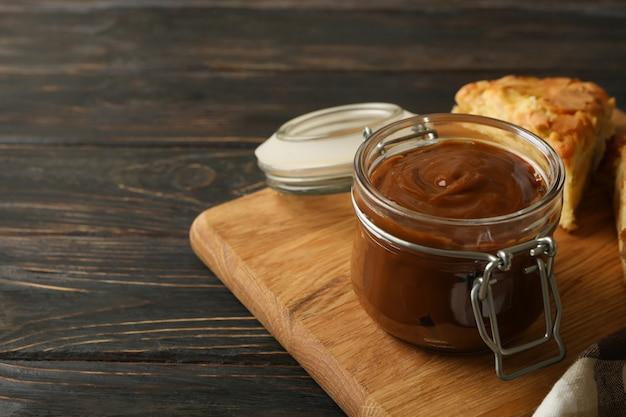 Junta con pastel y leche condensada de caramelo sobre superficie de madera