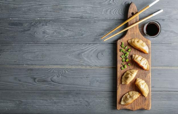 Junta con sabrosa gyoza japonesa en mesa de madera