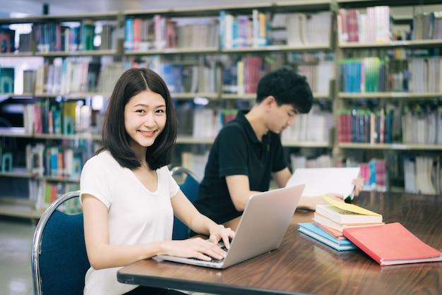 Junte a los estudiantes asiáticos felices con la computadora portátil y el libro que hablan en biblioteca en la universidad.