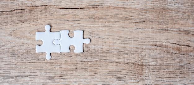 Junte las piezas del rompecabezas en el fondo de madera de la tabla. soluciones comerciales, objetivo de misión, éxito, objetivos, cooperación, asociación y estrategia.