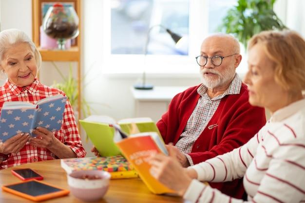 Junto con amigos. buen hombre barbudo sentado con un libro mientras tiene una reunión con sus amigos