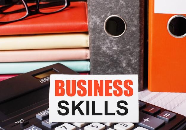 Junto a los diarios y carpetas con documentos en la calculadora hay una tarjeta blanca con la inscripción habilidades empresariales.