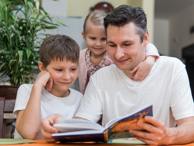 Junto familia con hermanos leyendo un libro