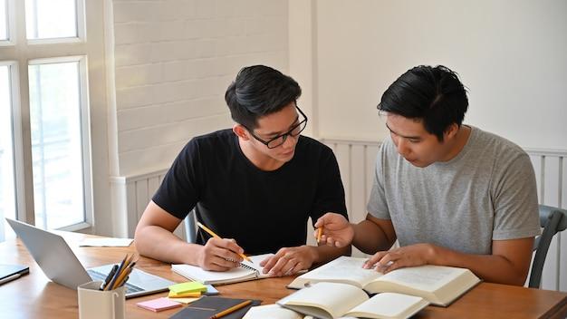Juntos lección de dos hombres con libros sobre la mesa.