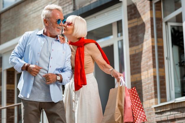 Juntos para siempre. elegante adorable mujer de pelo gris besando a su marido en la calle mientras sostiene varios paquetes con regalos