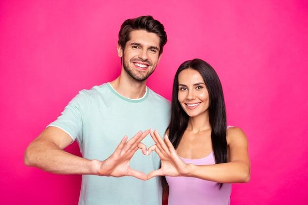 ¡juntos para siempre! foto de increíble chico y dama haciendo figura de corazón con brazos que expresan sentimientos usan ropa casual aislado fondo de color rosa