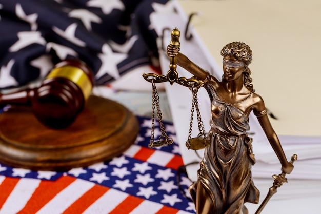 Justicia sosteniendo la balanza de la justicia con documentos inacabados en la mesa de la oficina legal en la bandera estadounidense oficina legal
