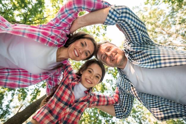 Justo debajo de la familia feliz formando un grupo en el parque