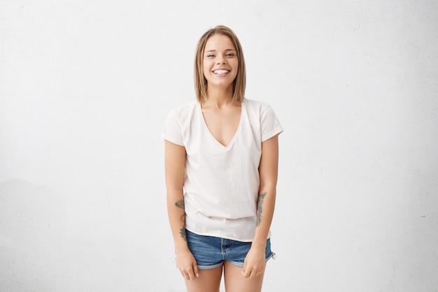 Juventud y felicidad. estilo y moda. atractiva mujer joven alegre de moda vistiendo camiseta blanca y pantalones cortos de jeans sonriendo ampliamente, feliz con buenas noticias positivas