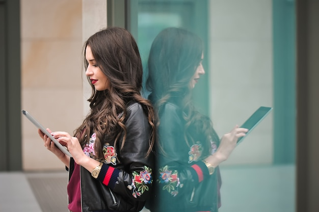 Juventud y tecnología. mujer joven atractiva que usa la tableta al aire libre.