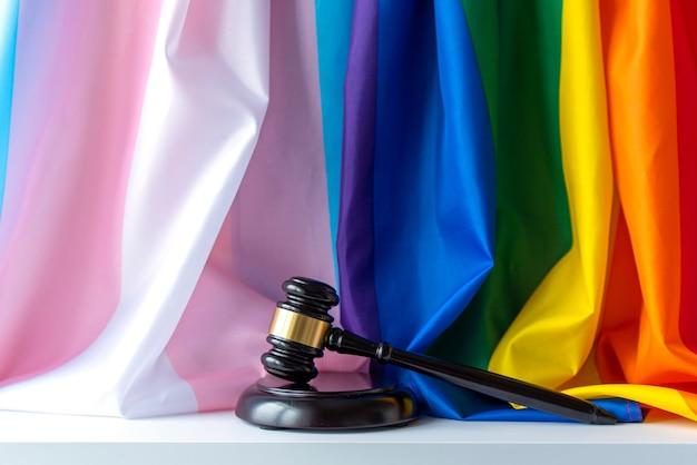Juzgar mazo de madera arco iris y banderas transgénero como símbolo de tolerancia
