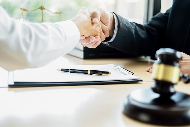 Juzgue el mazo con el abogado de la justicia que tiene reunión del equipo en la firma de abogados con el fondo de la oficina legal.
