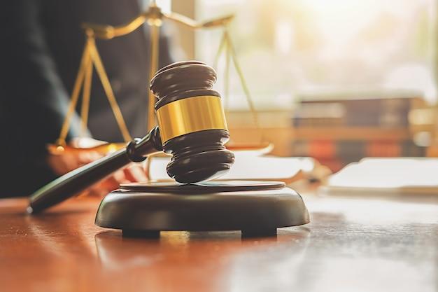 Juzgue el mazo con los abogados de la justicia que tienen reunión del equipo en el fondo del bufete de abogados.
