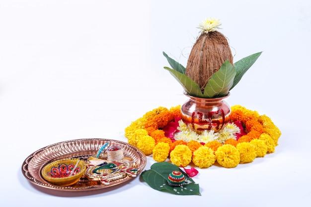 Kalash de cobre con coco, hojas y decoración floral sobre un fondo blanco