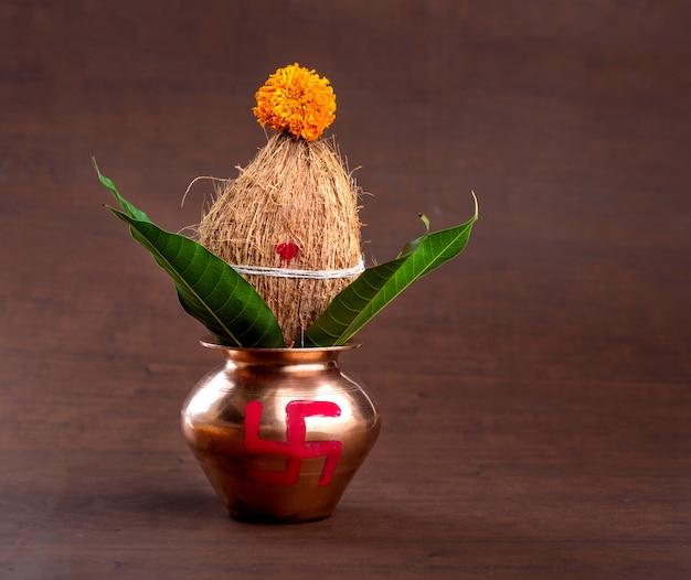 Kalash de cobre con hojas de coco y mango con decoración floral en una mesa de madera. esencial en puja hindú.