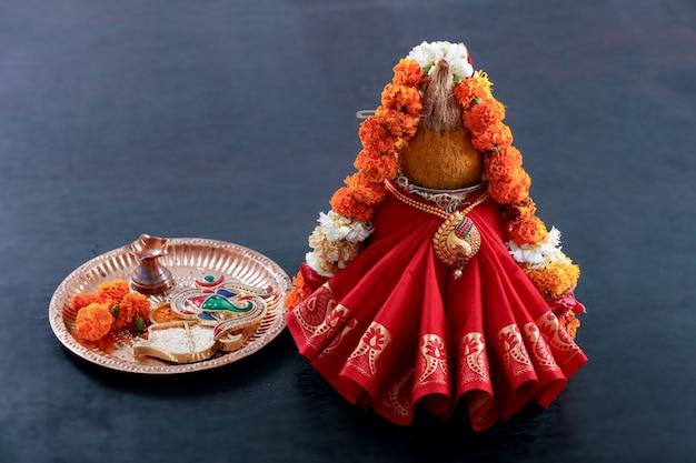 Kalash decorativo con coco y hoja con decoración floral.