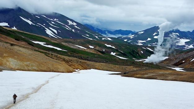 Kamchatka. foto de montañas y nieve. hierba verde, géiseres y turistas.