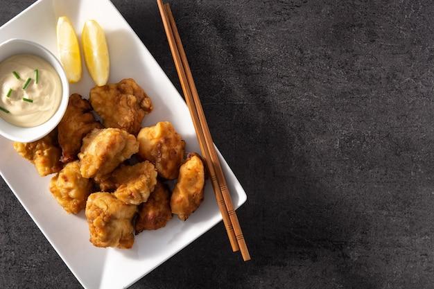Karaage de pollo picante sobre fondo de pizarra negra