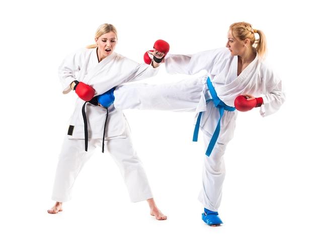 Karate de chicas rubias lindas se dedican a la formación en un kimono en blanco