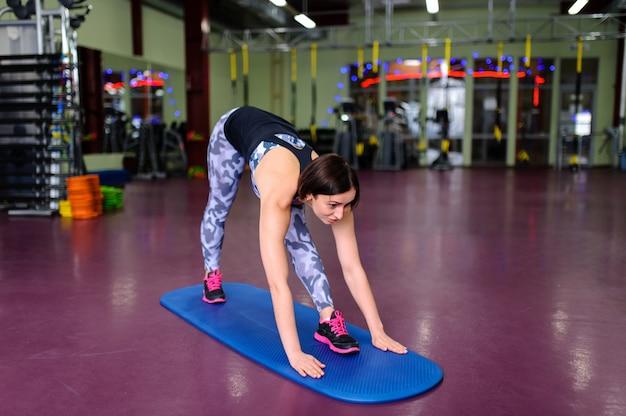 Karate hermoso de la muchacha en la estera en el gimnasio.