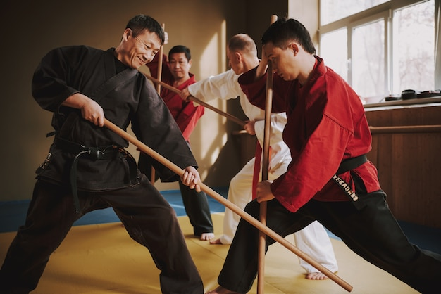 Karate luchadores de artes marciales luchando con palos.