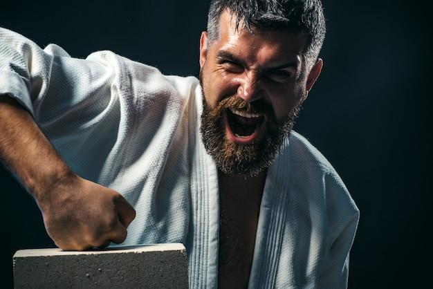 Karate masculino guapo muestra un retrato de puñetazo de luchador de artes marciales mixtas masculino guapo gritando