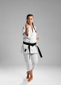 Karate mujer en acción aislado en fondo blanco.