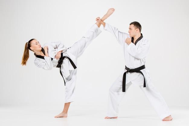 El karate niña y niño con cinturones negros