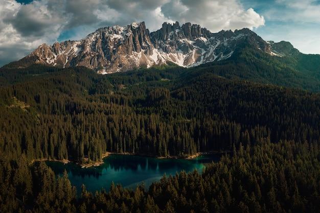 Karersee rodeado de bosques y dolomitas bajo un cielo nublado en italia