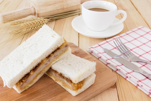Katsu sando, servir con servilleta, set de cubiertos y taza de café en mesa de madera