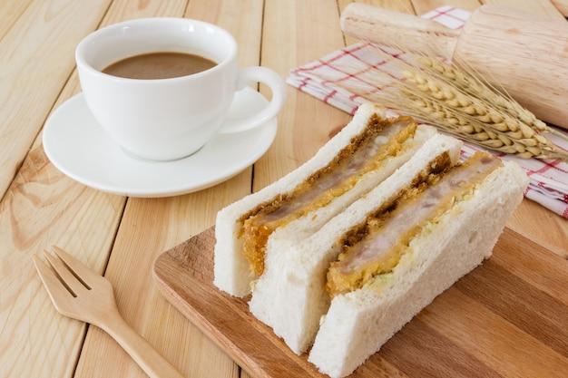 Katsu sando, sirve con servilleta, cubiertos y taza de café en el fondo de la mesa de madera