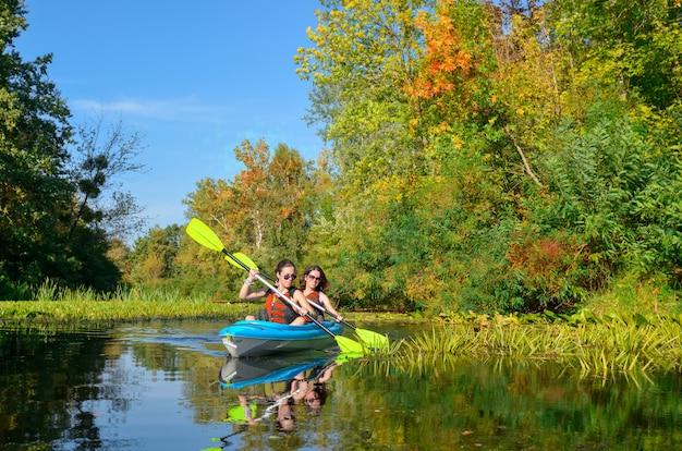 Kayak familiar, madre e hija remando en kayak en la excursión en canoa por el río divirtiéndose, activo fin de semana de otoño y vacaciones con niños, concepto de fitness