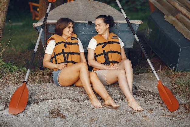 Kayak. una mujer en kayak. las niñas se preparan para pasear en un lago.