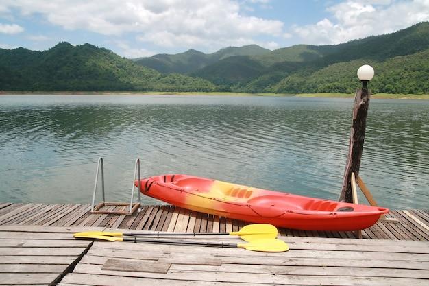 Kayak rojo con montaña y lago.