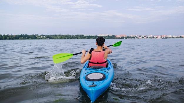 Kayaker salpicaduras de agua con remo mientras kayak